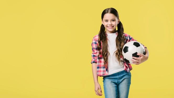 Chica posando con fútbol en estudio