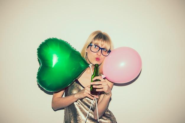 Chica posando con globos y cerveza