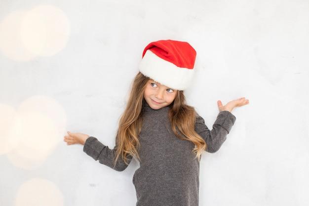 Chica posando moda con un sombrero de santa claus