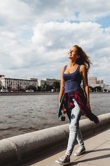 Chica posando con tabla de skate