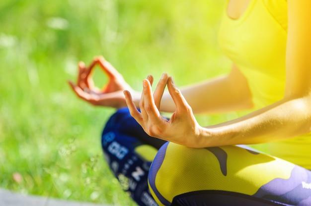 Chica posando yoga afuera en el bosque por la mañana
