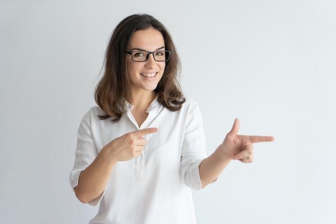 Chica positiva alegre en gafas recomendando nuevo producto o servicio.
