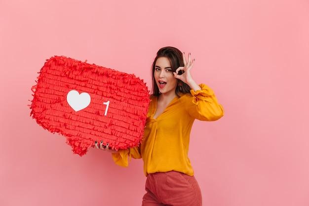 Chica positiva en blusa y pantalones brillantes sostiene como de intagram en la pared rosa y muestra el signo de ok.