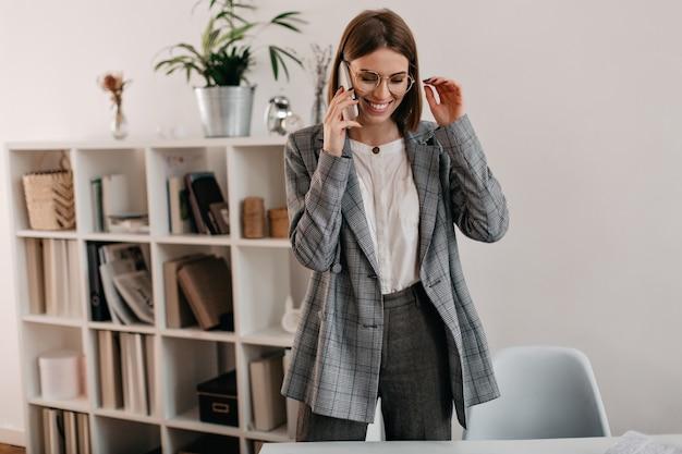 Chica positiva en chaqueta gris y gafas elegantes con sonrisa habla por teléfono en la oficina blanca.