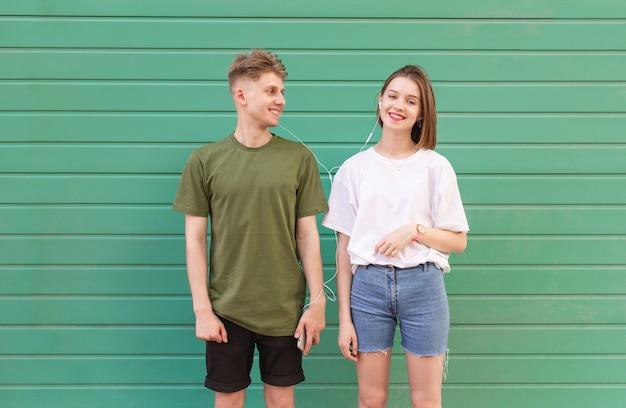 Chica positiva y un chico con una elegante ropa casual en un verde