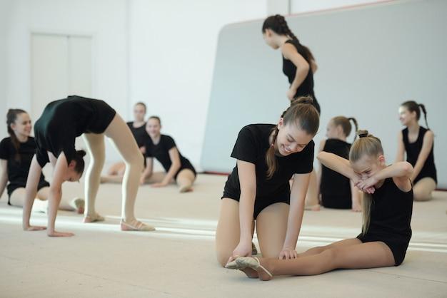 Chica positiva con cola de caballo empujando los dedos de los pies de un amigo mientras la ayuda a aumentar el punto de los pies en la clase de ballet