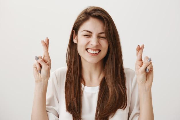 Chica positiva esperanzada cruzar los dedos mientras pide un deseo, sonriendo optimista