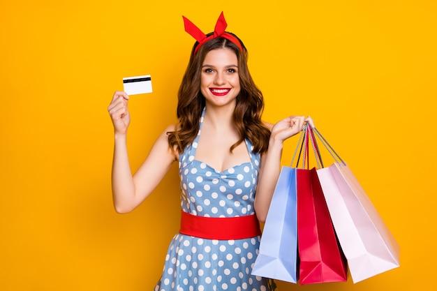 Chica positiva mantenga bolsas de compras pagar con tarjeta de crédito sobre fondo amarillo