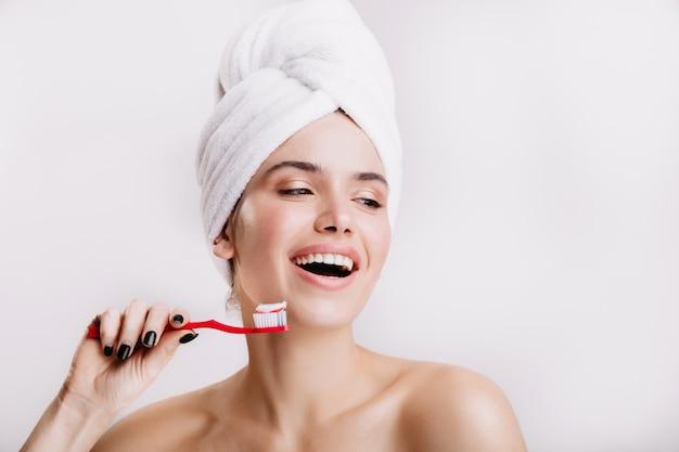Chica positiva sin maquillaje lindo sonríe en la pared blanca. mujer después de la ducha cepillándose los dientes.