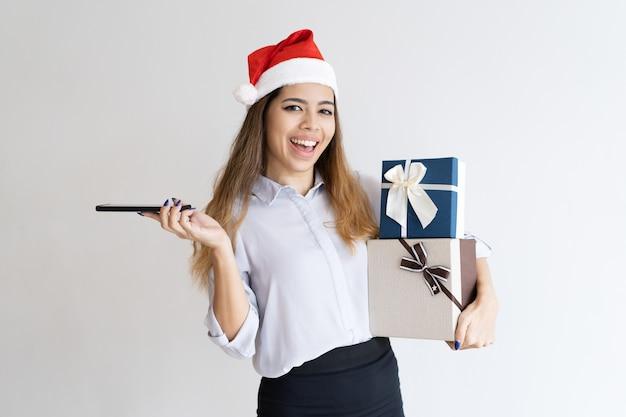 Chica positiva posando con regalos de navidad