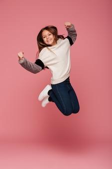 Chica positiva saltando y sonriendo aislado