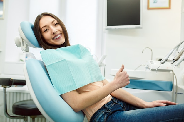 Chica positiva en la silla del dentista