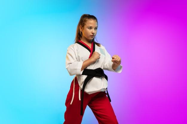 Chica practicando taekwondo con cinturón negro aislado en la pared degradada