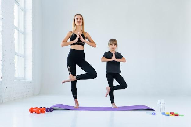 Chica practicando yoga, de pie en vrksasana ejercicio con namaste, pose de árbol. meditación femenina en el fondo blanco del estudio del desván.