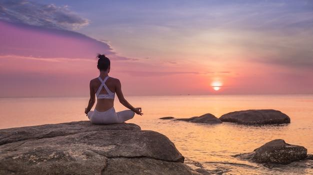 Chica practicando yoga en una roca