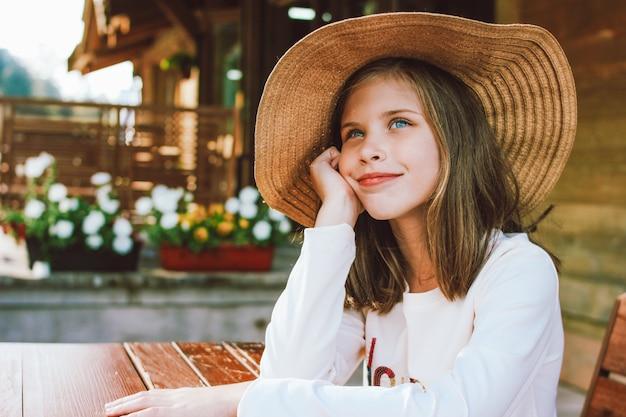 Chica preadolescente atractiva en sombrero de paja con ojos azules sentado y soñando en la mesa