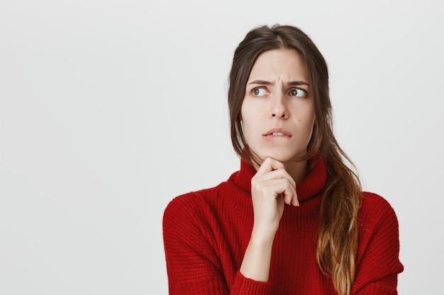 Chica preocupada pensando, mordida labio preocupada