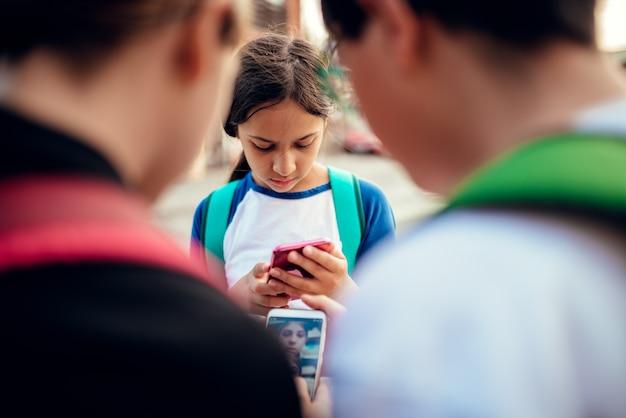 Chica preocupada de pie entre amigos y usando teléfonos inteligentes