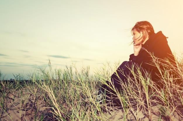 Chica preocupada sentada en la arena