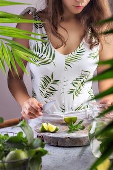 Chica prepara limonada de verano corta limón en el tablero