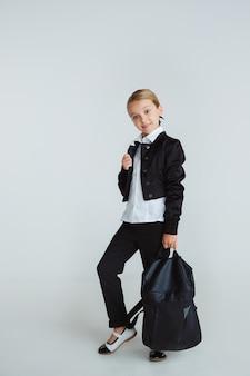 Chica preparándose para la escuela después de un largo receso de verano. de vuelta a la escuela. pequeño modelo caucásico femenino posando en uniforme escolar con mochila en la pared blanca. infancia, educación, concepto de vacaciones.
