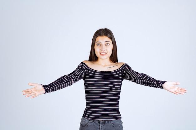 Chica presentando algo en su mano abierta.
