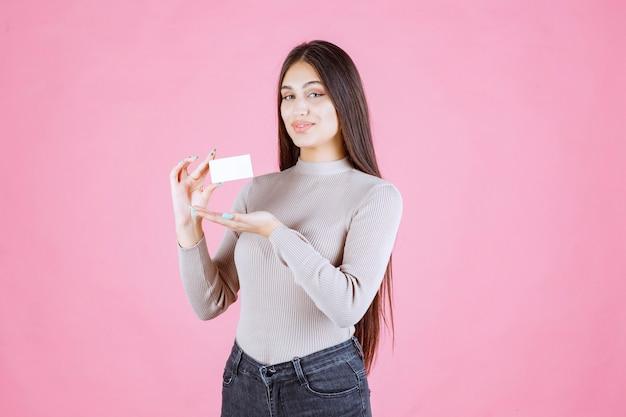 Chica presentando su tarjeta de visita a un socio comercial