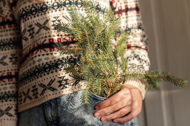 Chica de primer plano con lindo suéter y ramas de abeto