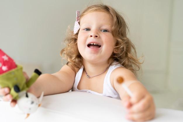 Chica de primer plano con piruleta y juguete