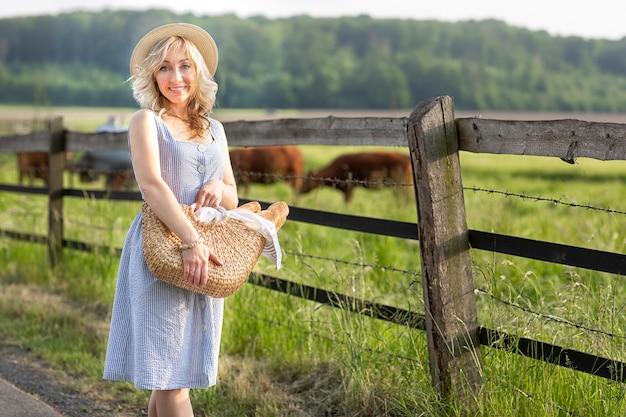 Chica del pueblo con una bolsa de leche y pan atravesando los campos con vacas pastando