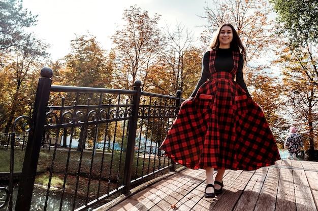 Chica en puente con vestido largo escocés rojo chica con cabello largo y castaño en el parque otoño