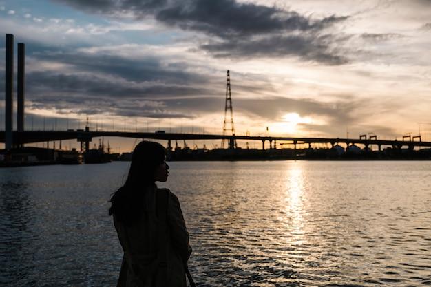 Chica puesta de sol en el mar y el puente