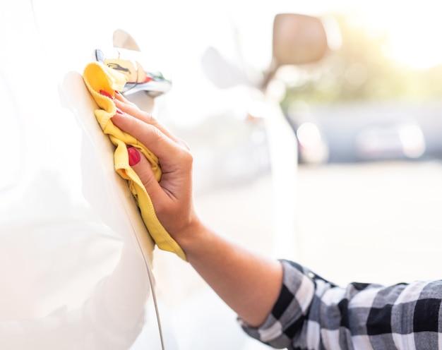 Chica pulir la puerta del coche cerrar
