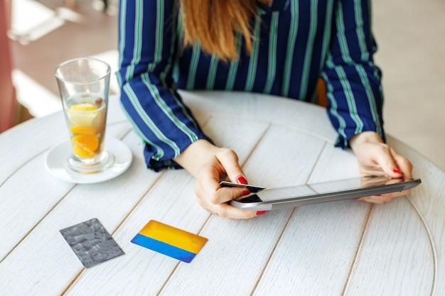 Chica que compra online con una tableta y una tarjeta de crédito.
