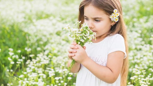 Chica que huele a flores silvestres en el prado
