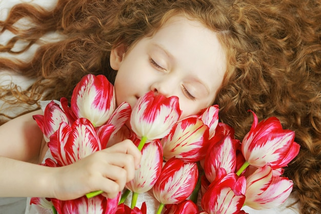 Chica que huele un ramo de tulipanes.