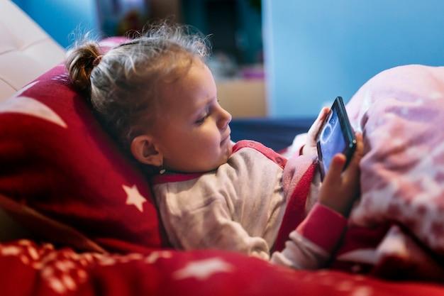 Chica que pone el juego de teléfono inteligente en la cama