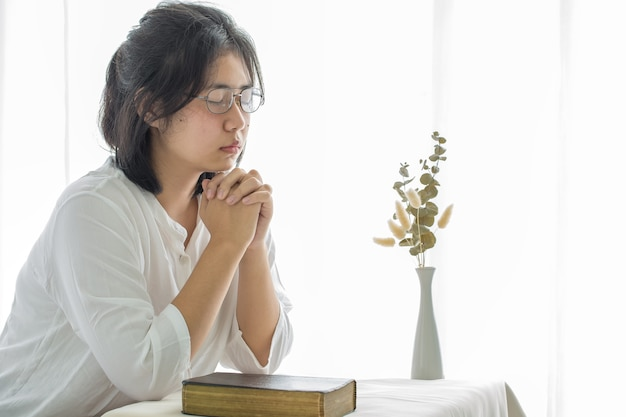 Chica quedarse en casa rezar y adorar a dios. adoración de la niña de oración y oración desde casa por la crisis del coronavirus. iglesia en casa, iglesia en línea, manos en oración, adoración en casa