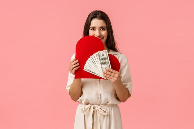 La chica quiere amor y dinero a la vez. sensual y atractiva, coqueta mujer morena vestida, con tarjeta de corazón y dinero en efectivo, se ríe como si tuviera mucho dinero y una relación romántica, de pie en la pared rosa