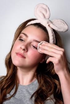 Chica quitando el maquillaje de la cara con un algodón en gris