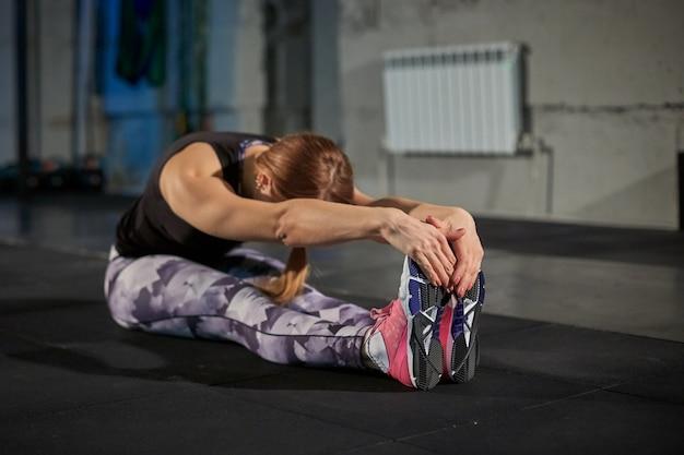 Chica r en polainas grises haciendo estiramientos. gimnasio deportivo de estilo industrial.