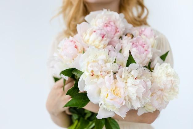 Chica con ramo de peonías rosas en pared blanca