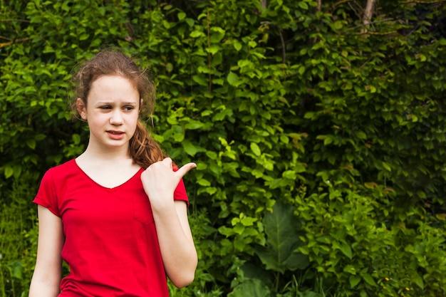 Chica rara apuntando hacia el lado con el pulgar hacia arriba en el parque