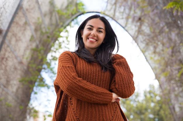Chica de raza mixta alegre en suéter caminando en el parque