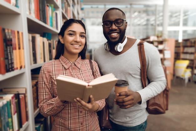 Chica de raza mixta india étnica y chico negro en la biblioteca