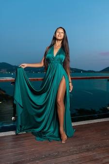 Chica de raza mixta con largo cabello negro posando en un vestido de noche color aguamarina.