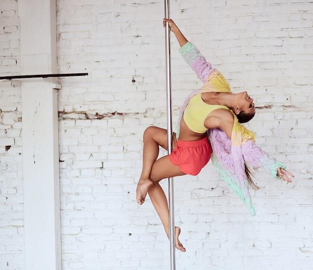 Chica realiza pole dance en el estudio con pared de ladrillo blanco