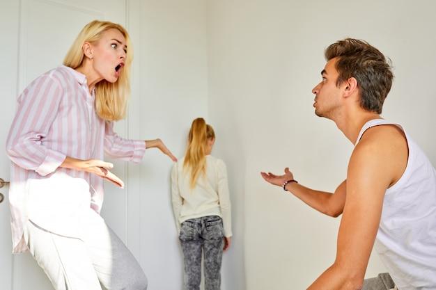 Chica rechazada cansada de soportar la pelea de los padres, de pie mirando a la pared en la esquina, hombre y mujer gritando en casa