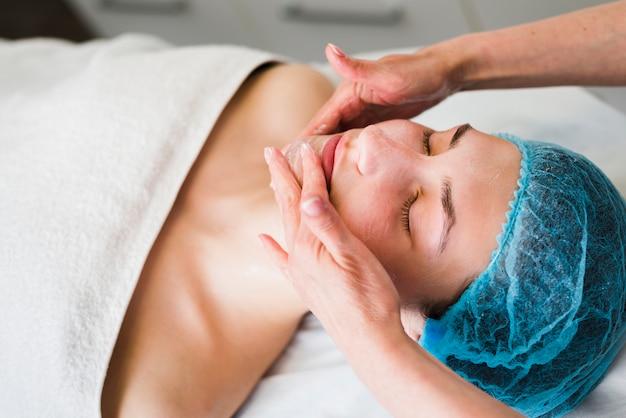 Chica recibiendo tratamiento facial en salón de belleza