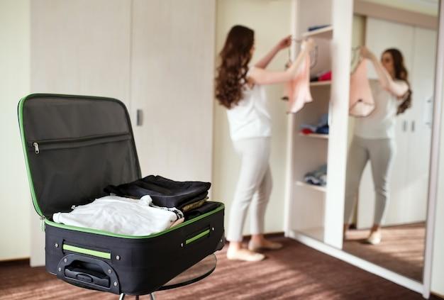 Chica recoge una maleta en una habitación de hotel.